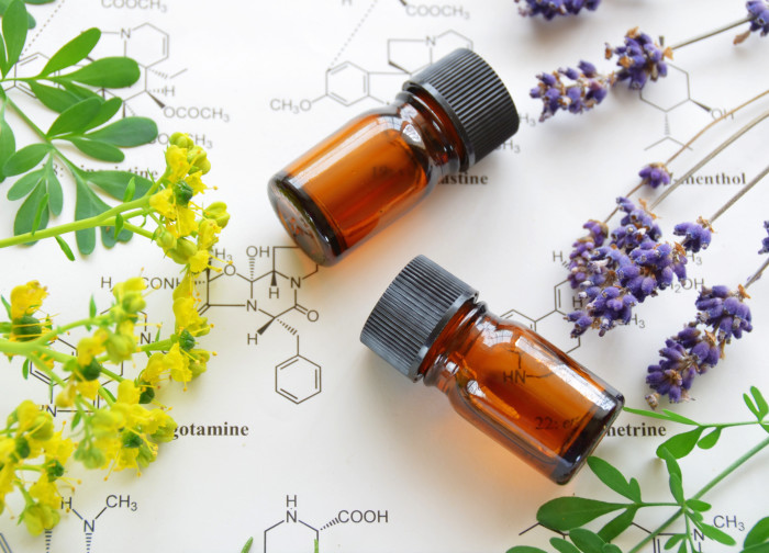 essential oils on science sheet with herbal flowers